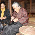 南海日日新聞〔写真〕イトバショウの繊維をつないで糸を作る与論民俗村の菊千代さん(右)と友子さん=12日、与論町