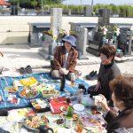 南海日日新聞〔写真〕墓前で酒席を囲む人々=16日、知名町田皆