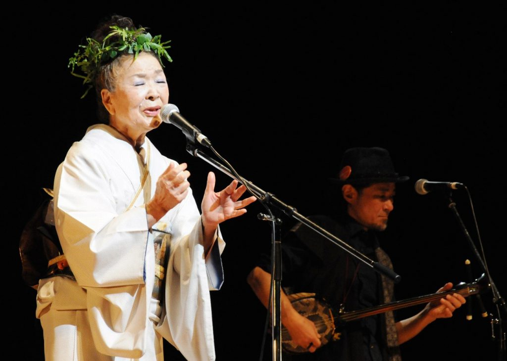 南海日日新聞〔写真〕シマ(古里)への思いを込め、島唄を歌う朝崎郁恵さん=25日、奄美市名瀬
