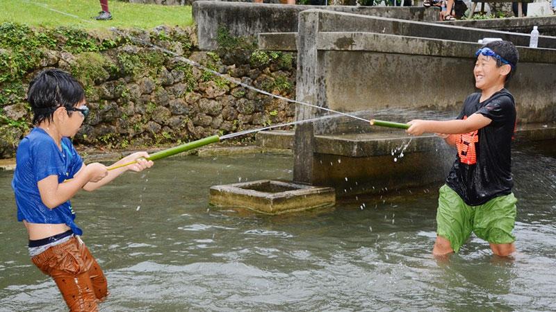 南海日日新聞〔写真〕ジッキョヌホーで水遊びを楽しむ子どもたち=21日、知名町瀬利覚