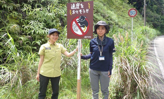 奄美野生生物保護センター提供:交通事故防止を呼び掛ける看板を設置した関係者ら=18日、瀬戸内町