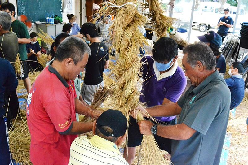 南海日日新聞〔写真〕大綱を編み込んでいく参加者=20日、与論町の城自治公民館