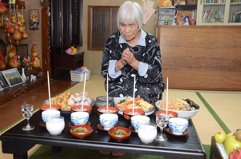 南海日日新聞〔写真〕ツカリの日に、赤飯などの料理を供え、コウソガナシに祈願する肥後サツさん=19日、龍郷町秋名