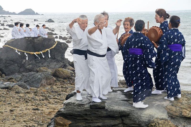 南海日日新聞〔写真〕小雨が降る中、海のかなたのネリヤカナヤの神々に祈りをささげる平瀬マンカイ=20日、龍郷町秋名