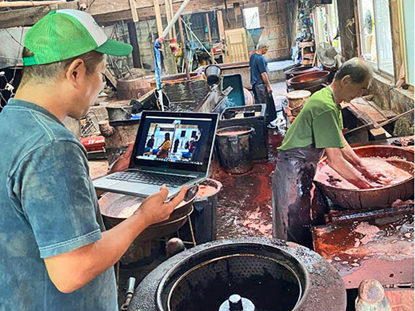 南海日日新聞パソコンで作業の様子を確認する山元さん(左)=28日、龍郷町戸口