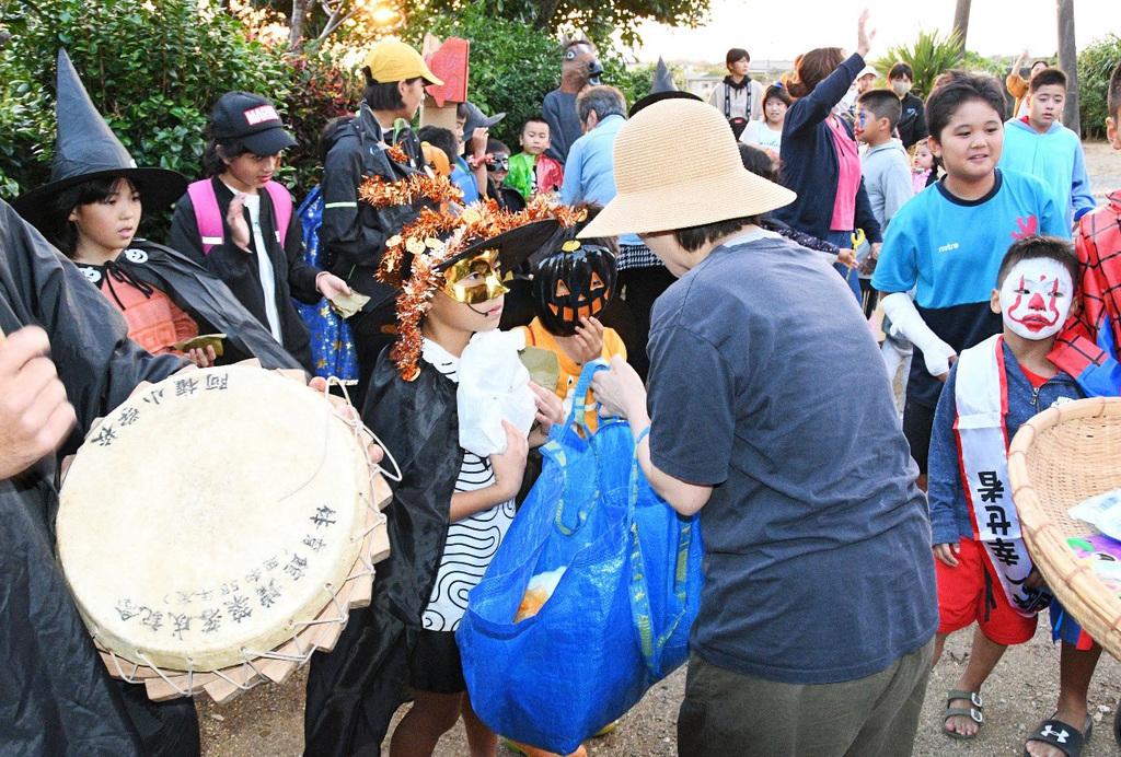 南海日日新聞〔写真〕踊りを終え餅やお菓子を受け取る仮装した子どもたち=10月31日、伊仙町阿権