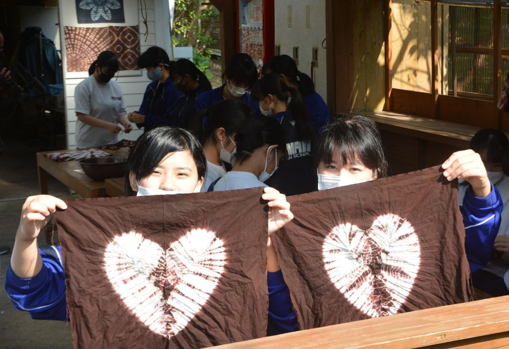 南海日日新聞〔写真〕見事な染め上がりに笑顔を見せる奄美高校の生徒=11日、大島紬村