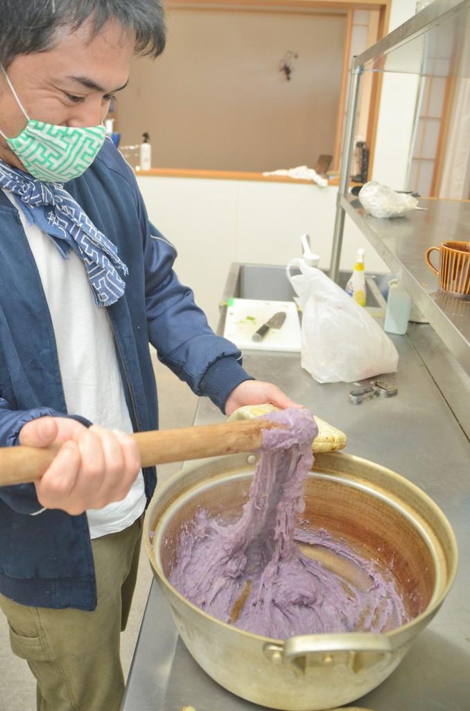 南海日日新聞南海日日新聞〔写真〕水煮したサツマイモと餅をすりこぎ棒で根気強く練りヒキャゲを作る荒波のやどりのスタッフ=18日、龍郷町幾里