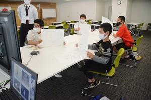 南海日日新聞〔写真〕画面に向かい、クイズに参加する児童生徒たち=23日、名瀬総合支所
